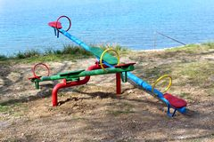 Colorful outdoor public playground equipment metal seesaw with wooden seats in local park next to calm blue sea in shade of old. Tree on warm spring day royalty free stock photography