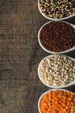 Colorful overhead view of grains in white spoon on wood Stock Photography