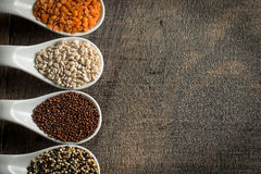 Colorful overhead view of grains in white spoon on wood Stock Photo