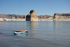 A colorful paddle board ready to be used at Lake Powell in the summertime. An inflatable surf board floating on the water at a scenic reservoir in the desert stock image