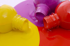 Colorful paint background. Closeup of spilling bottles of red, yellow and purple paint stock photos