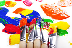 Colorful paint and brushes Stock Images
