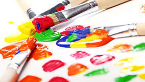 Colorful paint and brushes Stock Photos