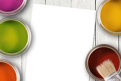 Colorful paint cans and blank white paper sheet Royalty Free Stock Image