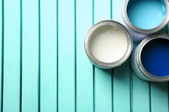 Colorful paint cans on blue wooden background, top view. Space for text royalty free stock image