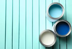 Colorful paint cans on blue wooden background, top view. Space for text stock photo