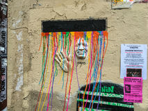 Colorful paint drips stream over wall art face and hand in Paris, France Stock Photos