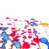 Colorful paint splashes over white paper. Background, closeup square photo with selective focus Stock Photography