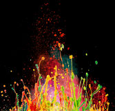 Colorful paint splashing. On black stock photo