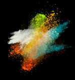 Colorful paint splashing. On black background stock images