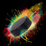 Colorful paint splashing. With hockey puckl isolated on black Stock Photography