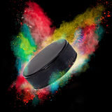 Colorful paint splashing. With hockey puckl isolated on black Royalty Free Stock Images