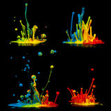 Colorful paint splashing. Isolated on black stock photography