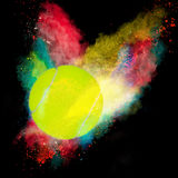Colorful paint splashing. With tennis ball  on black Royalty Free Stock Photos