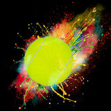 Colorful paint splashing. With tennis ball isolated on black Stock Photography