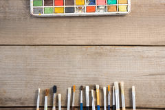 Colorful paintbrush and palette arranged on wooden surface Royalty Free Stock Images