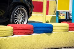 Colorful painted car tires standing in a row in front of a car wheel. stock image