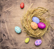 Colorful, painted decorative Easter eggs in the nest wooden rustic background top view close up Royalty Free Stock Photography