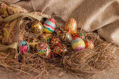 Colorful painted easter egg from fabric bag on hay Royalty Free Stock Photos
