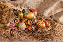 Colorful painted easter egg from fabric bag on hay Royalty Free Stock Photography