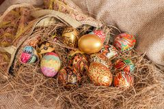 Colorful painted easter egg from fabric bag on hay Stock Image