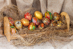 Colorful painted easter egg on hay in wooden shelf Stock Photos