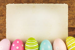 Colorful painted easter eggs with blank paper sheet stock photography