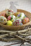 Colorful painted Easter eggs in brown wicker basket on branches, traditional Easter still life, painted flowers, wooden nest. Colorful painted Easter eggs in royalty free stock photo