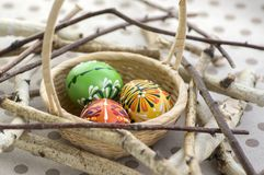 Colorful painted Easter eggs in brown wicker basket on branches, traditional Easter still life, wooden birds nest. Three colorful painted Easter eggs in brown stock image