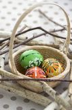 Colorful painted Easter eggs in brown wicker basket on branches, traditional Easter still life, wooden birds nest. Three colorful painted Easter eggs in brown stock photo