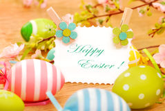 Easter eggs and greetings card on wooden background Royalty Free Stock Photos