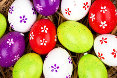 Colorful painted easter eggs hidden in a nest of straw Stock Photography