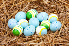 Colorful painted easter eggs hidden in a nest of straw Royalty Free Stock Image
