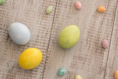 Colorful Painted Easter Eggs and Jelly Beans. On wood background Royalty Free Stock Images