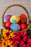 Colorful painted Easter eggs lie in a basket with flowers, on a wooden background. Colorful painted Easter eggs lie in a basket with flowers stock image