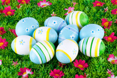 Colorful painted easter eggs located on a meadow with flowers Stock Photo