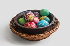 Colorful painted Easter eggs in a woven straw basket on white background stock photo