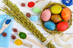 Colorful painted eggs in a nest of twigs of willow on a light background and multicolored rice for decorative painting. Stock Photography