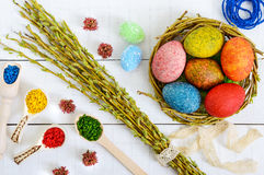 Colorful painted eggs in a nest of twigs of willow on a light background and multicolored rice for decorative painting Stock Photography
