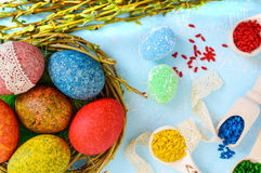 Colorful painted eggs in a nest of twigs of willow on a light background and multicolored rice for decorative painting. Royalty Free Stock Image