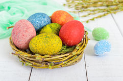 Colorful painted eggs in a nest of twigs of willow on a light background. Royalty Free Stock Image