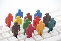 Colorful painted group of people figures on computer keyboard stock photography