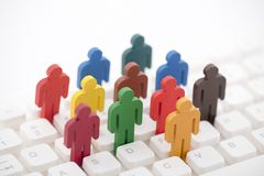 Colorful painted group of people figures on computer keyboard stock photo