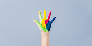 Colorful painted hand and fingers on blue background. Royalty Free Stock Photography