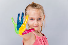 Colorful painted hands in a beautiful young girl. Royalty Free Stock Image
