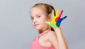 Colorful painted hands in a beautiful young girl. Stock Image