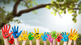 Colorful painted hands in front of a spring scene Stock Photography