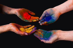 Colorful painted hands, holding holi isolated. On black royalty free stock photography