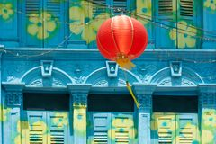 Colorful painted colonial house in Singapore with red lampion in front. Colorful painted house in blue Color with yellow and green Flowers and red Lampion in stock image