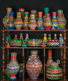 Colorful painted pottery crafts stacked in wooden storage shelve Royalty Free Stock Photography